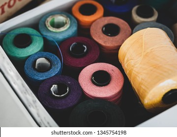Close up of thread cotton bobbins in box, selective focus.