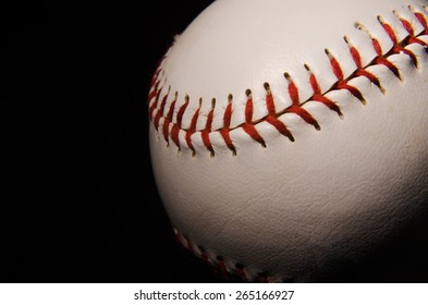 A close up of the threads of a single baseball on a black backdrop with single light illuminating it for isolation and drama.