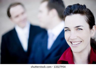 close up of three attractive businesspeople smiling and talking