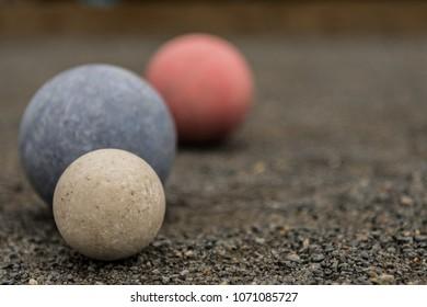 Close Up of Three Bocce Balls With White In Focus on gravel