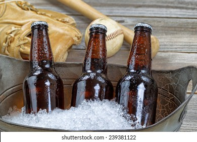 Close up of three brown cold bottled beers, crushed ice in metal container, and baseball equipment in background on rustic wood