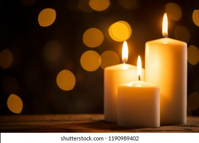 Close up of three burning candles on the wooden table with blurred Christmas light background