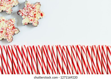 Close up of  three chocolate peppermint bark snowflakes with row of red and white striped peppermint candies with blank space for text