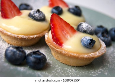 Close up of three French desserts. Little tarts with custard, fresh berries and powdered sugar. Tartlets with strawberries, blueberries served with icing sugar (castor sugar) on gray and white plates