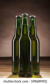 Close up of three glass bottles of beer on wooden table and brown background