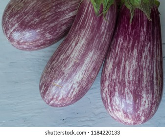 Close up of three graffitti eggplants on white rustic wooden background