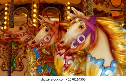 Close up of three hand painted carousel horses or gallopers on a fairground ride in an amusement park. illuminated background with mirrors. England.
