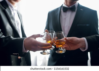 Close up of three hands of men in suits clink glasses of whiskey drink together in restaurant. Wedding day. Business concept. Alcoholic beverage