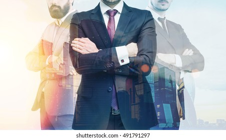 Close up of three man standing with their arms crossed against large city panorama. Concept of CEO. Toned image. Double exposure