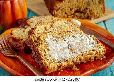 Close up of three slices of fresh baked pumpkin bread with butter on pumpkin shaped plate with cup of coffee sitting on blue wooden table