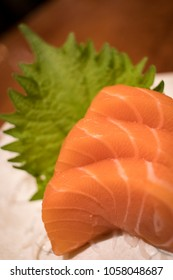 Close up of three slices of salmon sashimi on a white dish with shiso leaf at a sushi restaurant in London