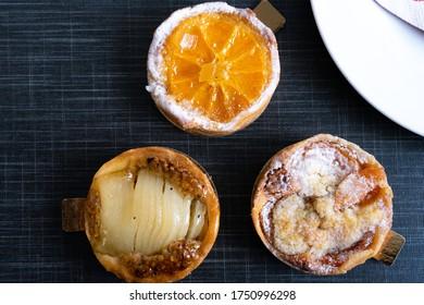 Nahaufnahme von drei verschiedenen Arten von Französischsteinen mit Früchten und Zuckerpulver in Draufsicht