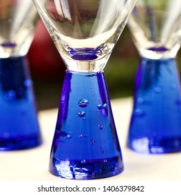 Close up of three vibrant cobalt blue shot glasses with shiny glass ready to be filled.