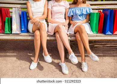 Close up of three women in white sneakers sitting on bench with shopping bags