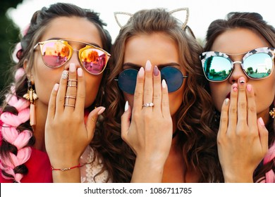 Close up of three young girls wearing in creative sunglasses with designed manicure, two lady covers mouth and one hiding face by hands. Happy friends posing and having fun together.