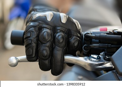 Close up of throttle control hand and brake lever motorcycle,Hands wearing black leather gloves with a protective card grip the brake lever.