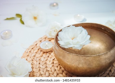 Close up Tibetan singing bowl with floating in water rose inside. Burning candles, flowers petals on the white wooden background. Meditation and Relax. Exotic massage. Copy space