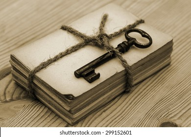 Close up of tied with twine bundle of old paper with old rusty weathered metal door keys on old rustic wooden table background, sepia