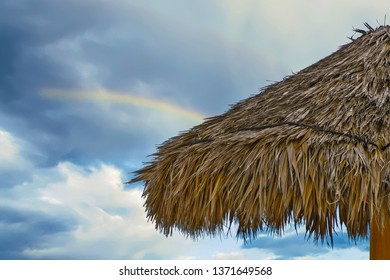 close up of tiki hut thatched roof with rainbow in sky background