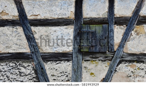 Close up of a timbered house with a little Window with closed wooden shutter