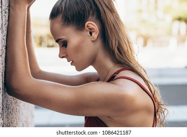 Close up of tired female athlete leaning on a wall outdoors. Profile view of sportswoman resting on a wall outdoors after a workout.
