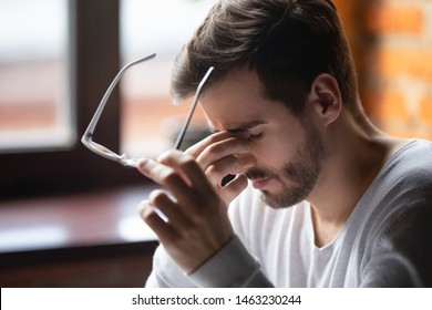 Close up of tired male take off glasses massage eyes feel fatigue suffering from strong headache, exhausted unwell man having eyestrain or astigmatism overwhelmed with work. Health problem concept