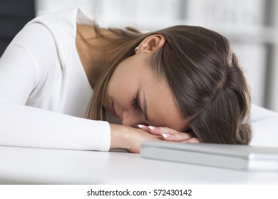 Close up of a tired woman wearing white clothes and sleeping near her laptop in an office with white and green binders.