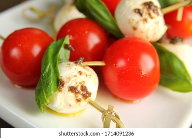 Close up of tomato,  bocconcini and fresh basil on skewer with balsamic and olive oil