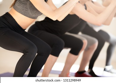 Close up of toned athletes standing on mats do squats together in fitness studio, fit men and women perform exercises, work on buttocks muscles, sportive people workout in gym. Healthy life concept