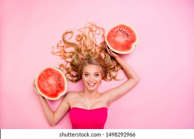 Close up top above high angle view photo beautiful she her lady lying down holding fruit big red half melons volume hair amazing pretty tender seductive body isolated pink background