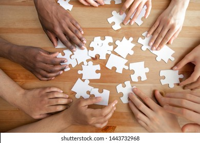 Close up top above view diverse male and female hands assembling puzzles together on table. Multiracial connection, logical thinking, students teamwork cooperation, business strategy concept.