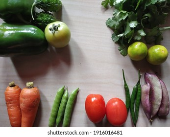Close up and top angle view of different types of fresh vegetables like capsicum, lemon, coriander leaves, green chili, carrot, tomatoes, broad beans, green peas.