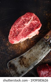 Close up top blade steak cut near butcher cleaver knife on a rustic metall background top view layflat.