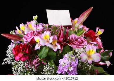 Close up of the top of a boquet of flowers with a blank greeting card.