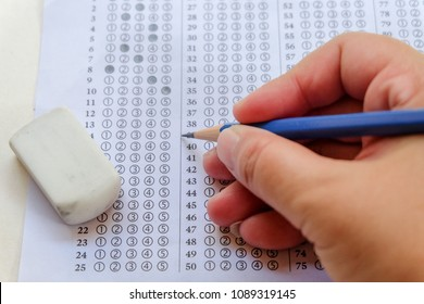 Close up and top view: Answers sheet with blue sharp pencil in hand and rubber isolated on white background. Top view of them. Take the exam timely concept. (selective focus)