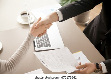 Close up top view of business handshake, male and female hands shaking over office desk after signing contract, holding signed statement, sealing deal as good result of successful negotiations