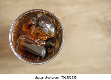 Close up top view of cola soda in a glass with ice cube on left of frame
