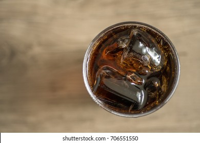 Close up top view of cola soda in a glass with ice cube on right of frame