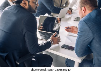Close up top view of confident business men of different race and ages, working together, man looking on blueprint, talking, using laptop duting meeting in the office