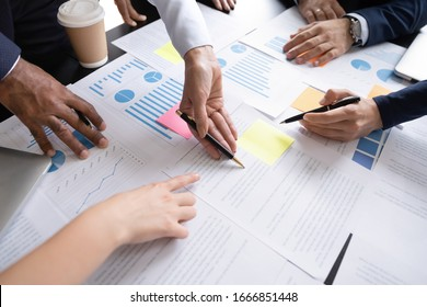 Close up top view of diverse businesspeople cooperate work together discussing company financial statistics, multiracial colleagues employees collaborate brainstorm with finance document at meeting