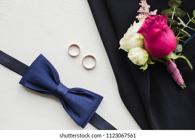 Close up top view of elegant modern formal male accessories. Blue bowtie, two golden wedding rings, flower boutonniere pinned to black jacket of suit. Set for wedding isolated on white background.