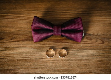 Close Up top view of elegant stylish red male bow tie and two golden rings isolated on a brown background. Preparation for wedding day concept.