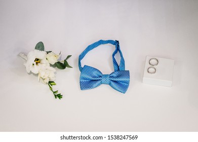 Close up top view of elegant stylish blue male bow-tie, flowers and two golden rings isolated. Preparation for wedding day concept.