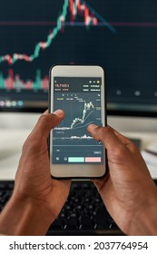 Close up top view of ethnic male trader use smartphone computer check financial graph chart money balance. Man investor exert trace online on stock market exchange. Cryptocurrency concept.