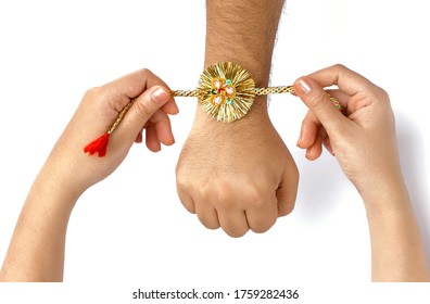 Close up top view of female  hands tying colorful rakhi on  her brother's hand isolated on white background on Raksha Bandhan Festival
