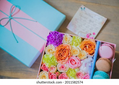Close up top view of gift box with flowers and colorful macaroons at flower shop. Floristry, handmade, wedding, birthday, dessert, biscuit, sweet food and traditional french cuisine concept
