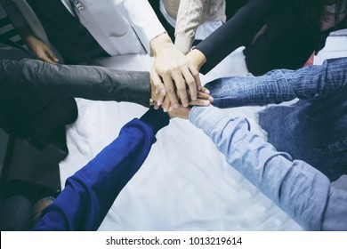 Close up top view of Group of Diverse Hands Together Joining Concept. Friends with stack of hands showing unity and teamwork.