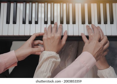 Close up top view hand teaching paino, teacher touch student hand to press the key on keyboard.