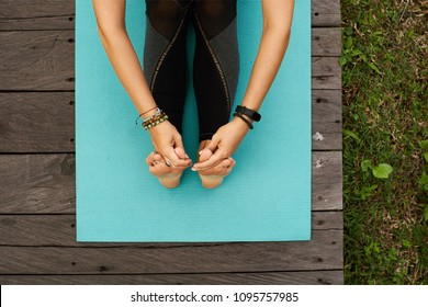 Close up Top view to hands holding foot of a female sitting on a yoga mat outdoors on a wooden floor