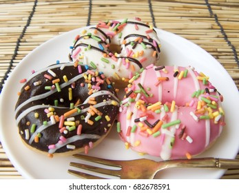 Close up top view of Mini donuts fancy with colorful sugar topping on a white plate and Rattan palm mat background.